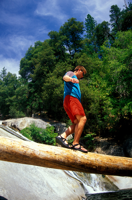 Timothy balancing on a log crossing a creek