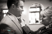 Mom helping the groom with his boutonniere