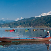 Man in boat on Lake Pokhara below Annapurna