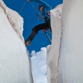 Climber crossing a crevasse on Mount Rainier