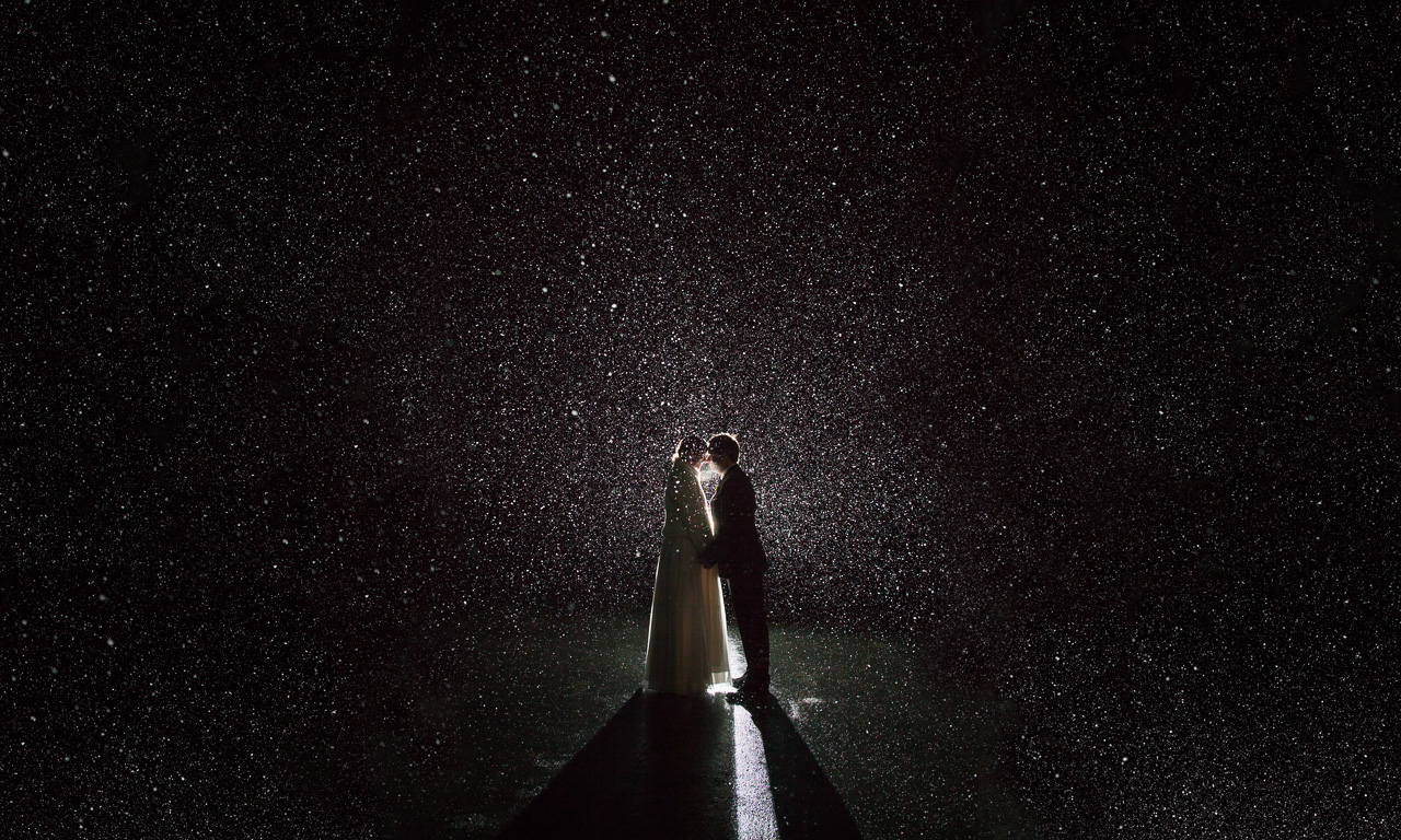 Newlyweds during snowfall