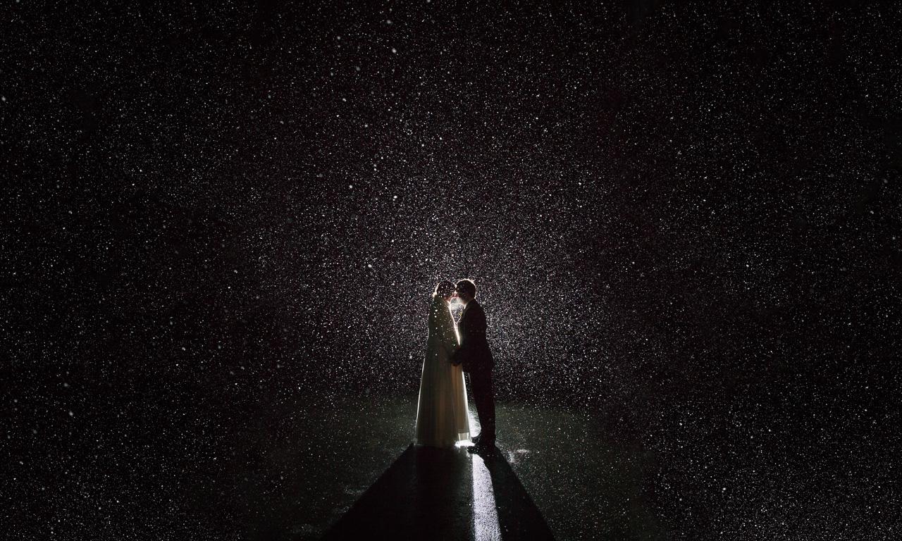 Newlyweds during snowfall