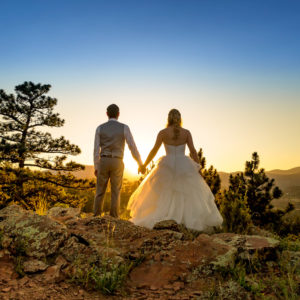 Portrait of a bride and groom holding hands and facing a setting sun in Boulder, Colorado.